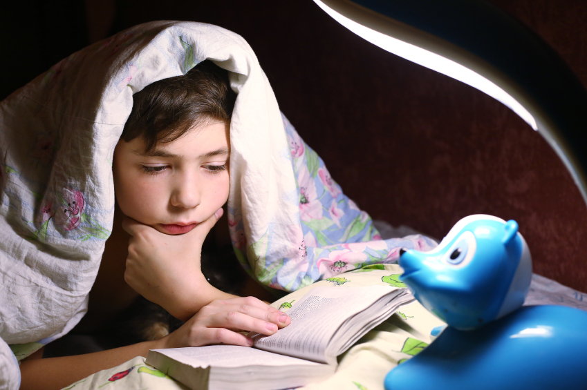 teen boy engaged in intriguing reading book under the blanket in night hour